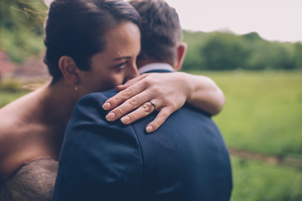 Couple hug with engagement ring in focus