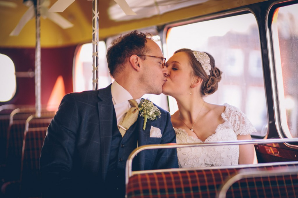 Bride and groom on routemaster kissing