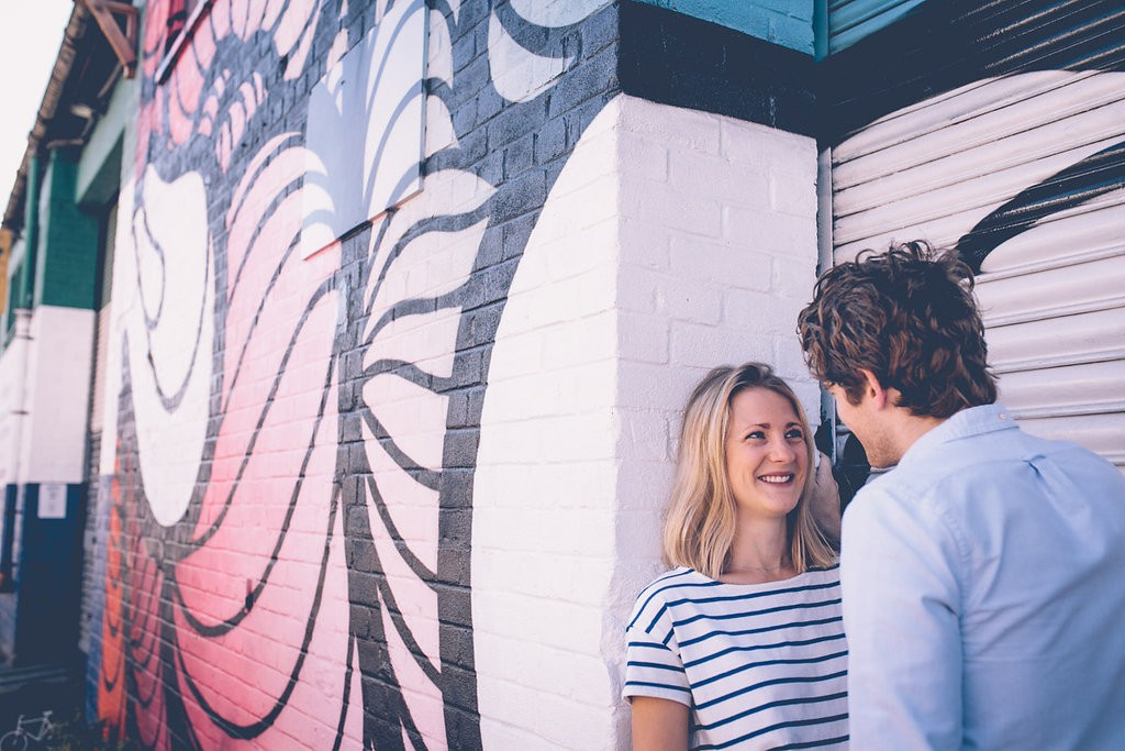 Couple against graffiti wall