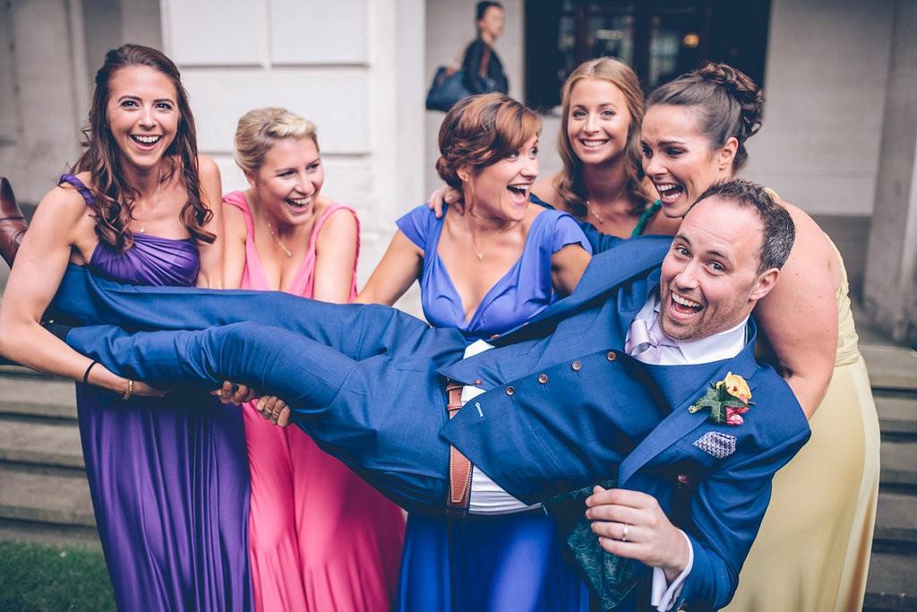 Bridesmaids lifting up groom