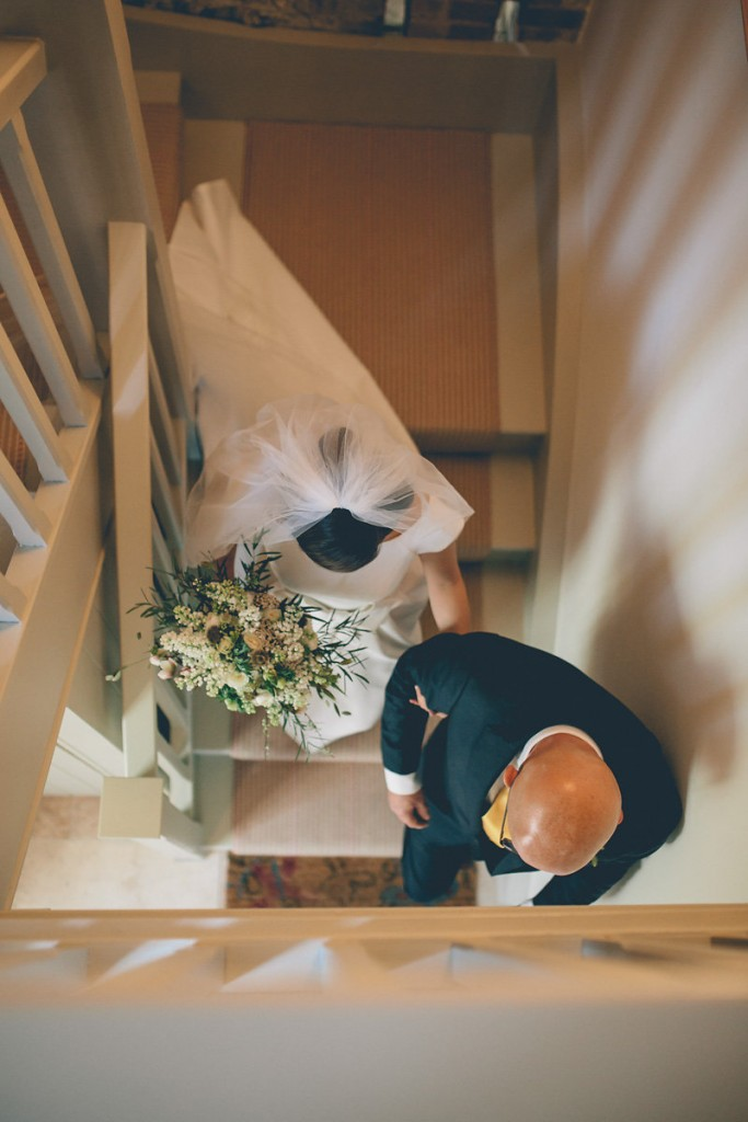 Bride walking downstairs with father