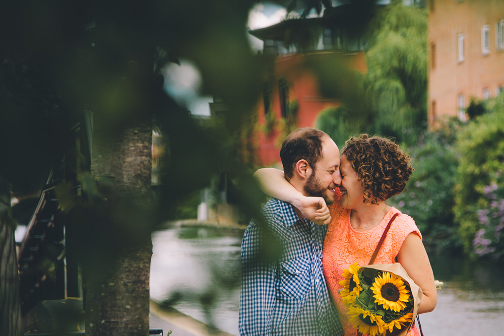 engagement shoot couple hugging with sunflowers