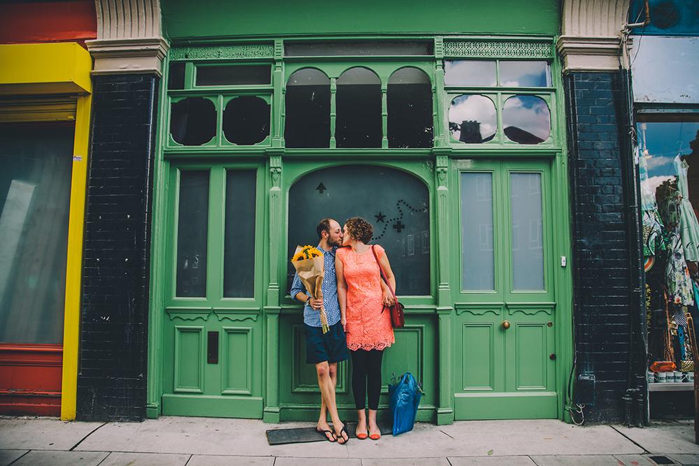 engagement shoot couple in doorway kissing