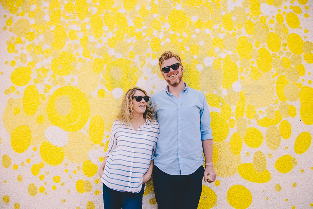 engagement shoot couple against yellow wall