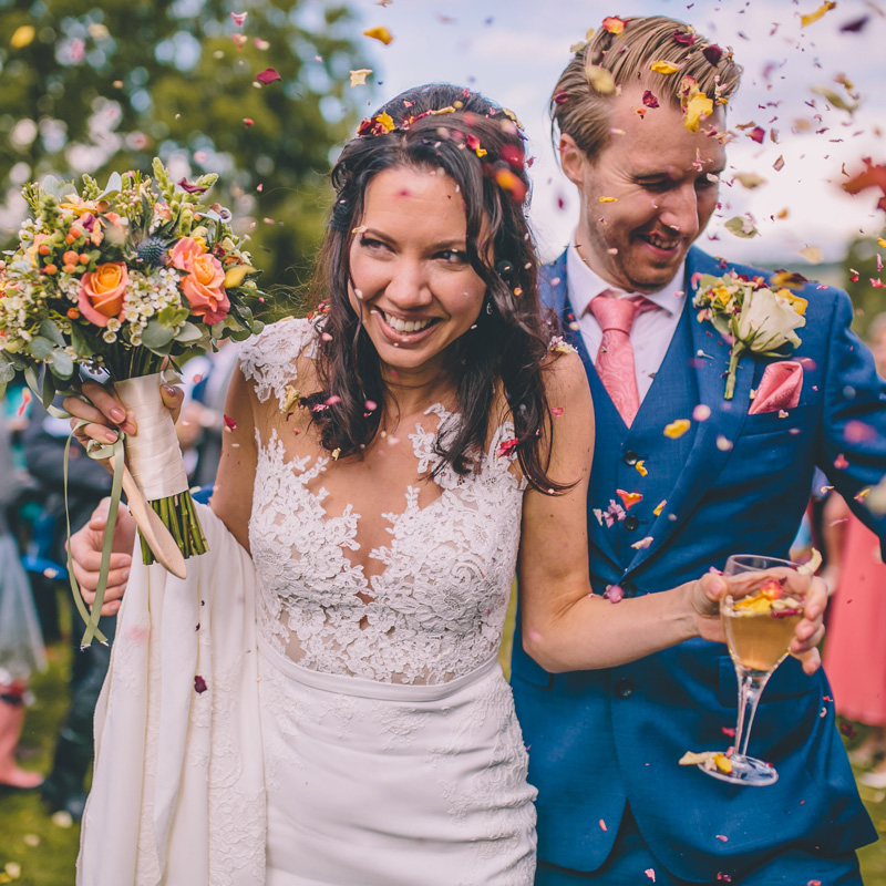 wedding photographer couple covered in confetti