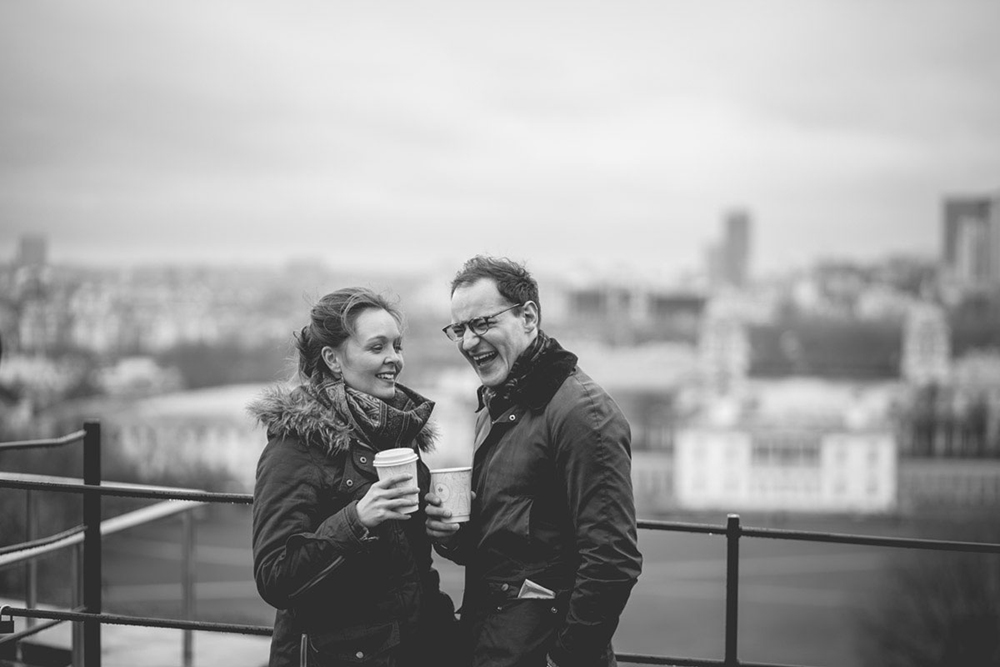 engagement shoot couple with coffees laughing