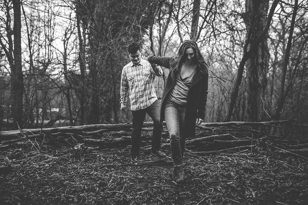 engagement shoot couple walking through woods