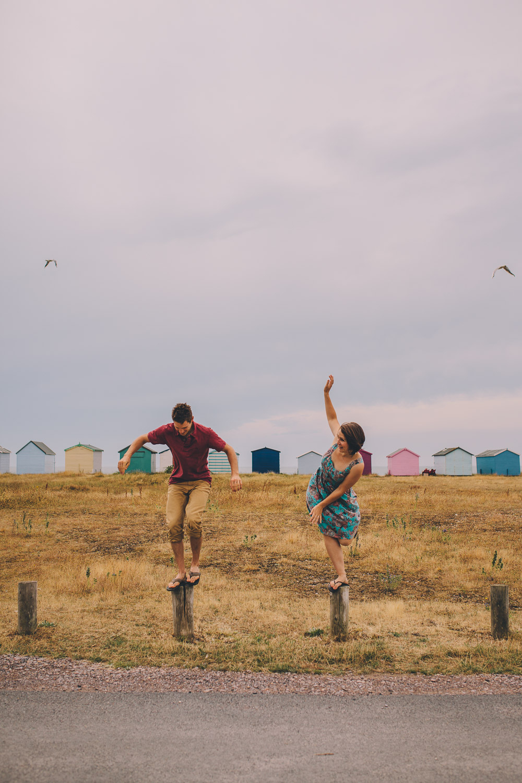 engagement shoot couple balancing on posts at beach