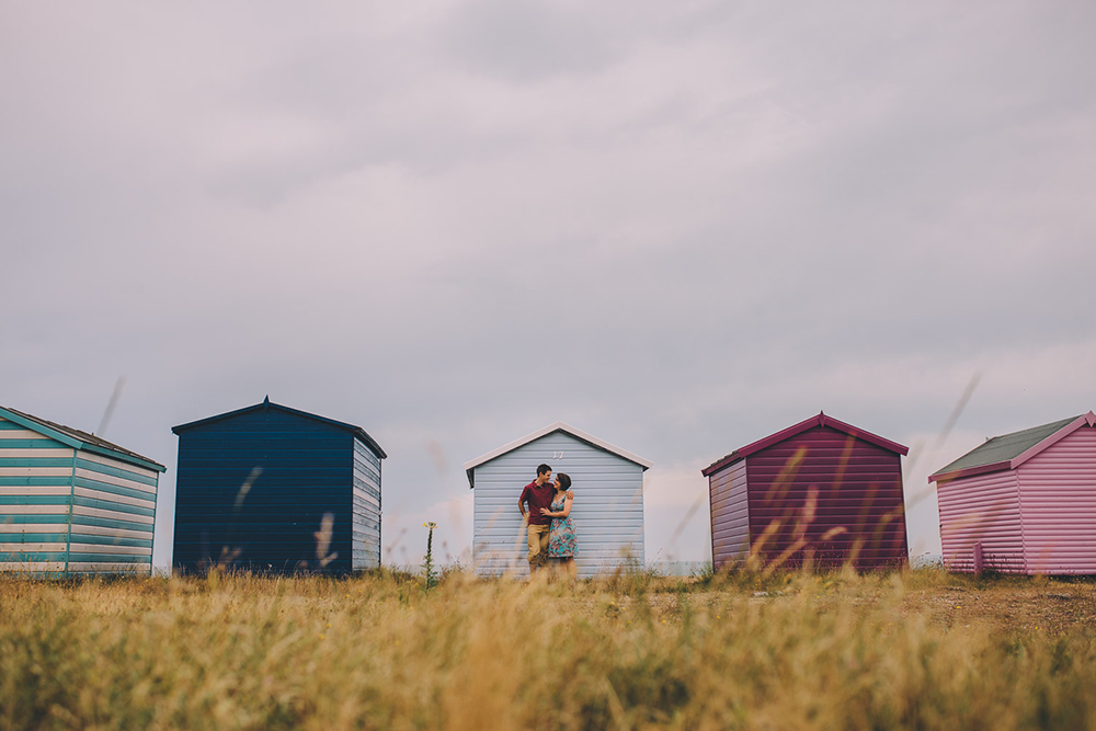engagement shoot couple in front of beach huts