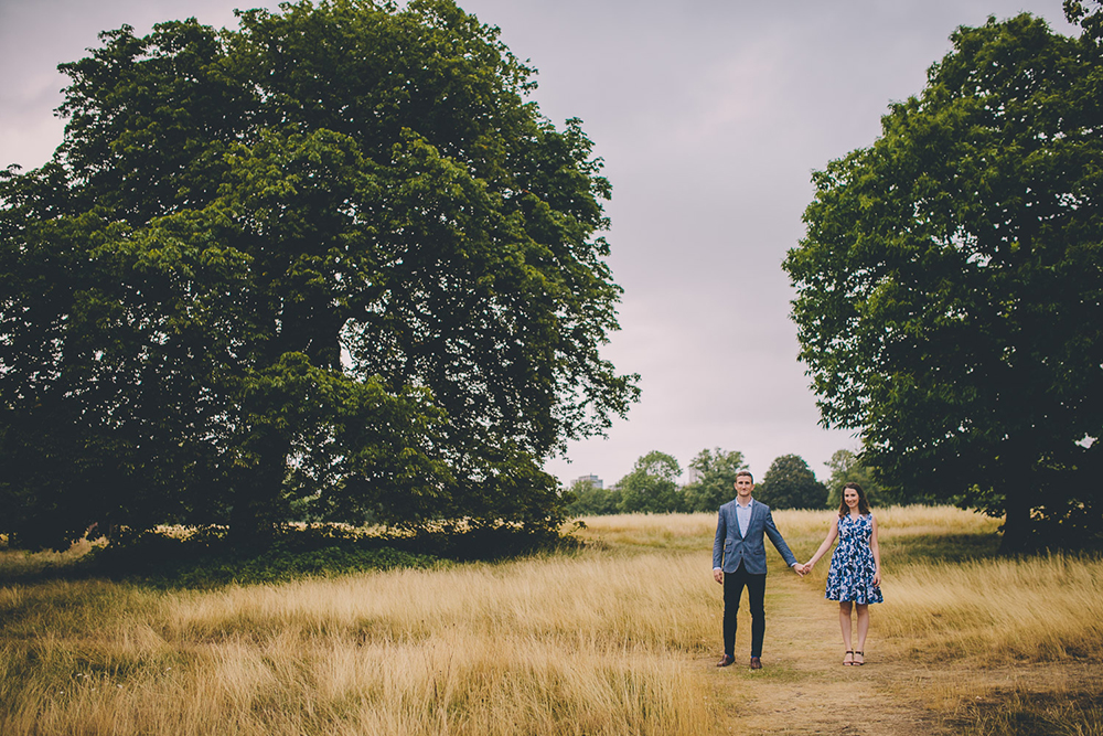 engagement shoot couple in long grass holding hands