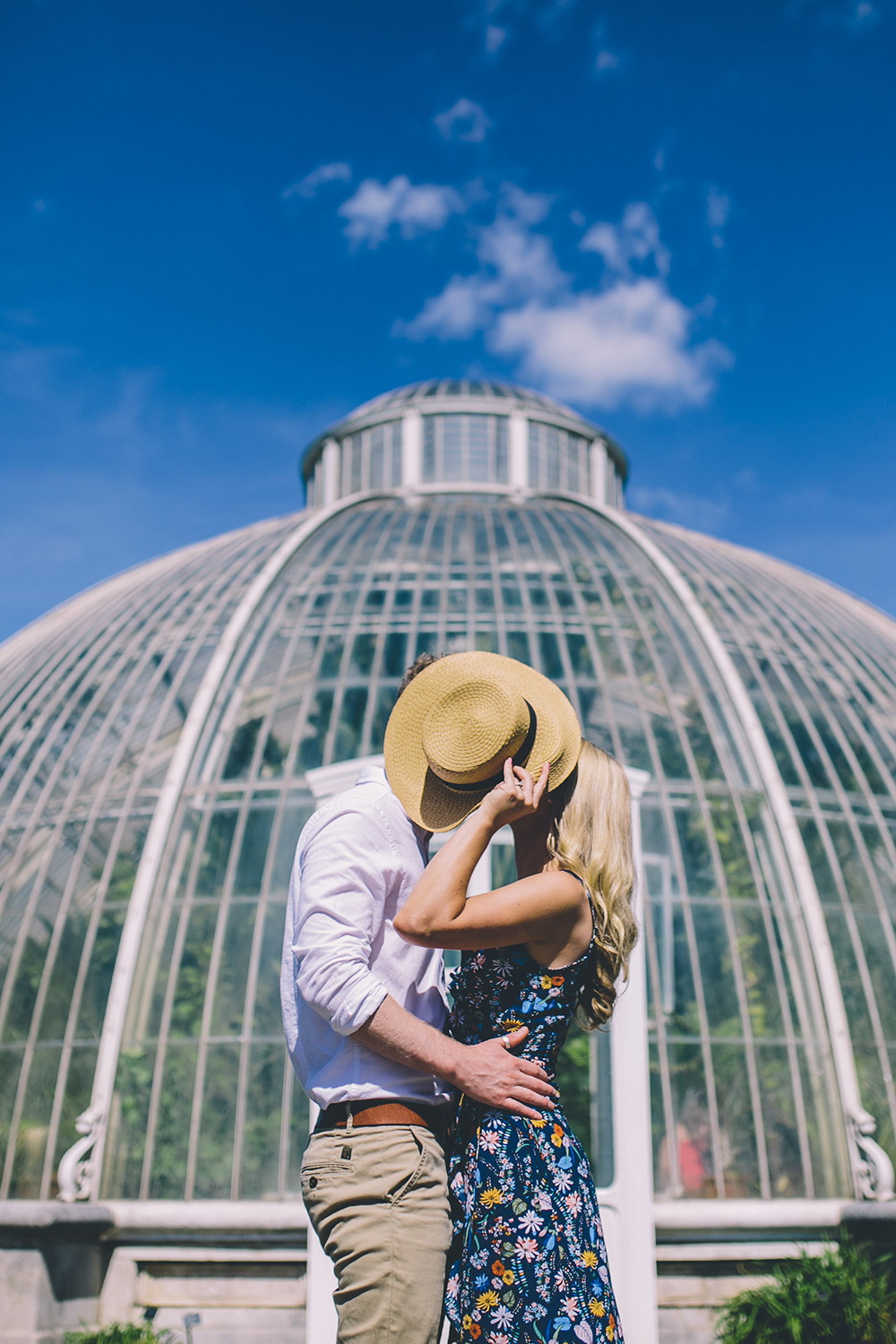 engagement shoot in front of glasshouse with hat