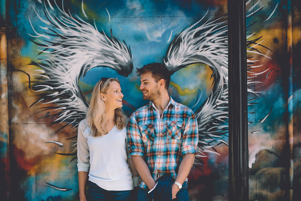 engagement shoot couple in front of grafitti