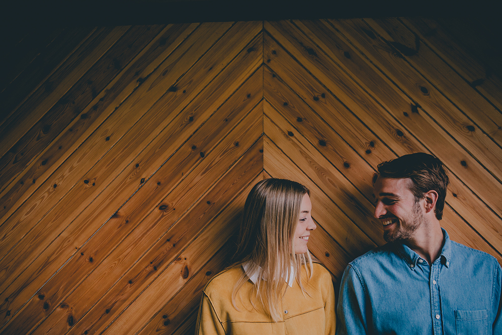 engagement shoot couple in front of wooden backdrop