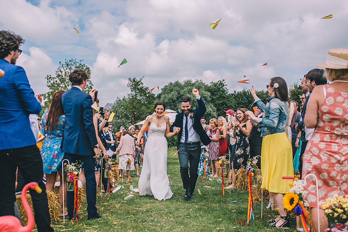 couple running through paper aeroplanes wedding photography
