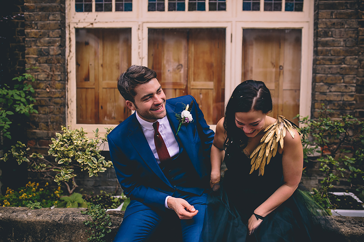 couple laughing sat on wall wedding photography