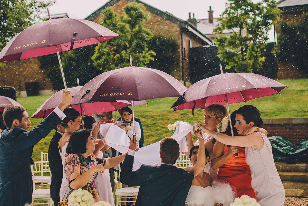 people rushing with umbrellas to shield the bride and groom wedding photography