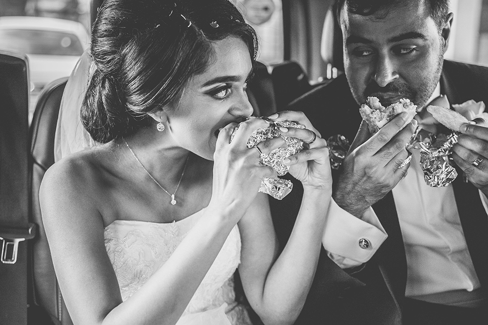 bride and groom eating sandwiches